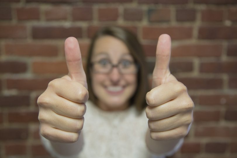 Very happy woman giving thumbs up after health coaching