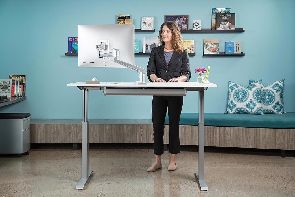 fit middle age woman standing with good posture at a standing desk in a blue office