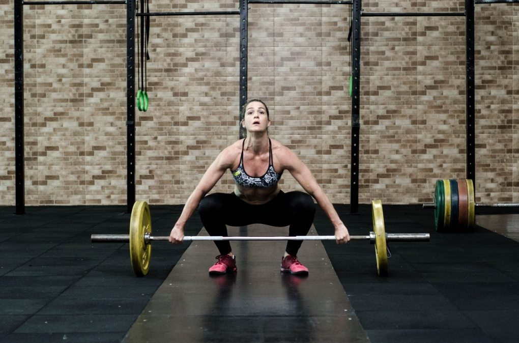 Fit and healthy middle age woman doing a snatch barbell exercise for stretch and power training