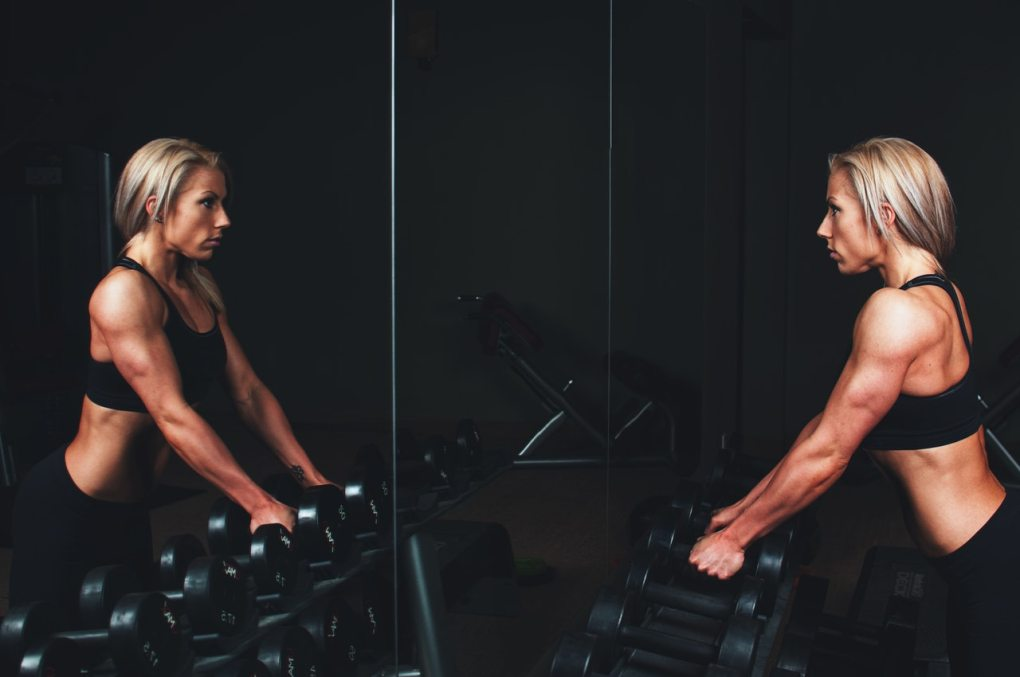 Fit and healthy lean woman in a crop top standing at a barbell rack at a gym