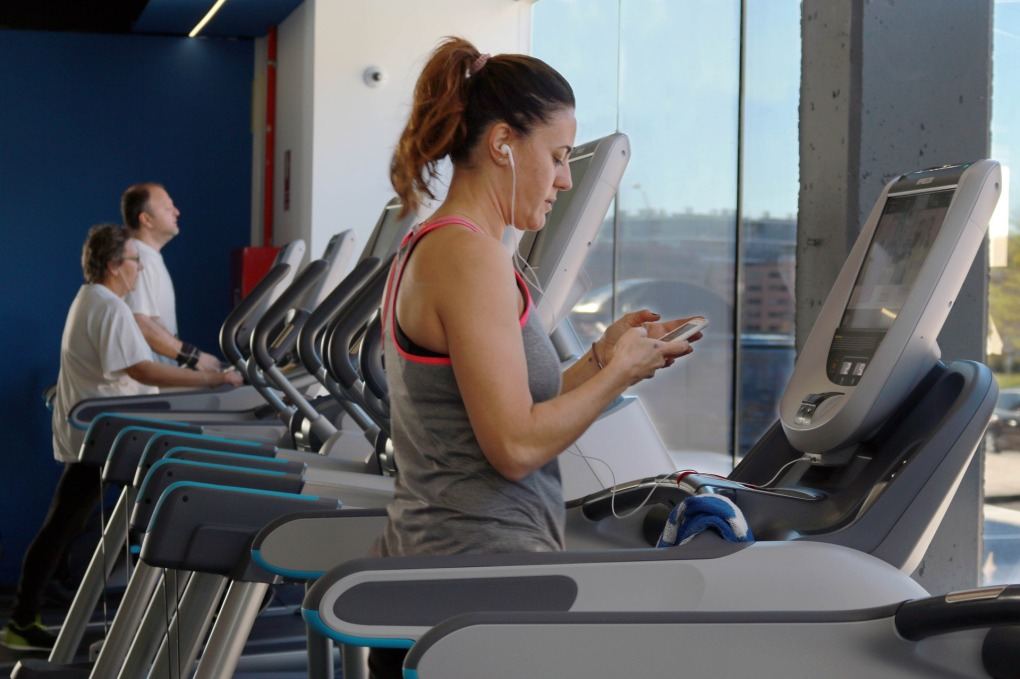 Fit and healthy middle age woman getting ready to run on a treadmill in a gym for a cardio workout