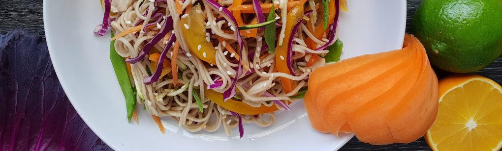 A fast healthy lunch of Asian soba noodle salad or soup with chicken and vegetables