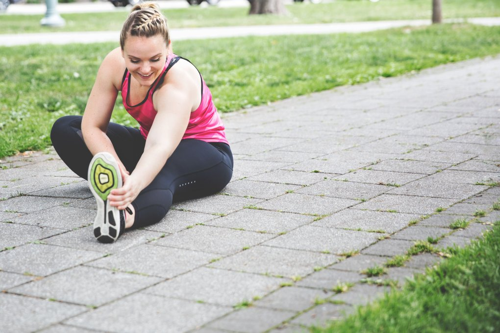 Healthy woman in late 30s getting ready to exercise by stretching hamstrings