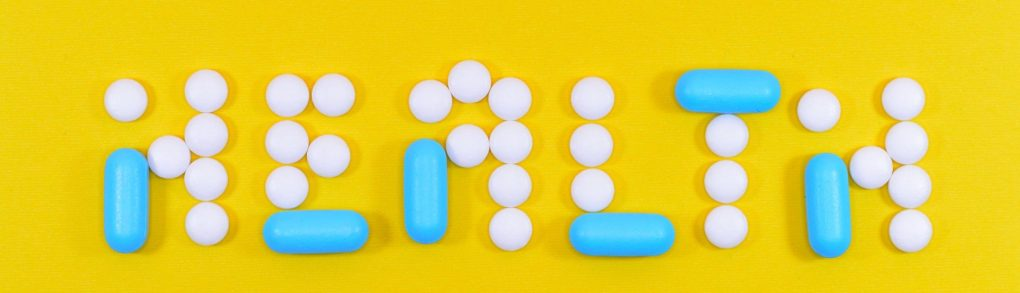 The word health spelled with blue and white pills on a yellow background